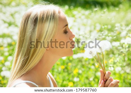 Girl blowing on white dandelion among dandelions - stock photo