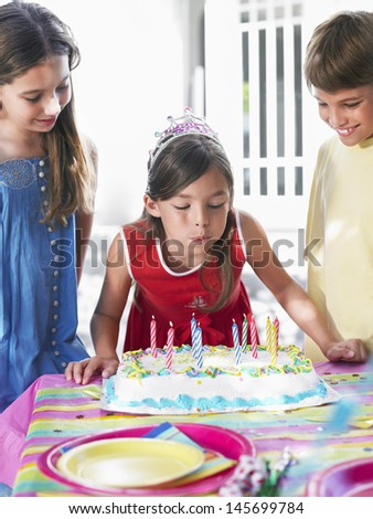 Girl blowing out birthday candles at the outdoor party