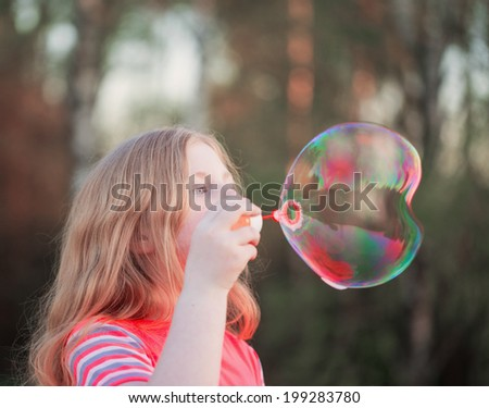 girl blowing soap bubbles outdoor - stock photo