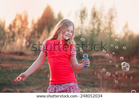 girl blowing soap bubbles outdoor at sunset - stock photo
