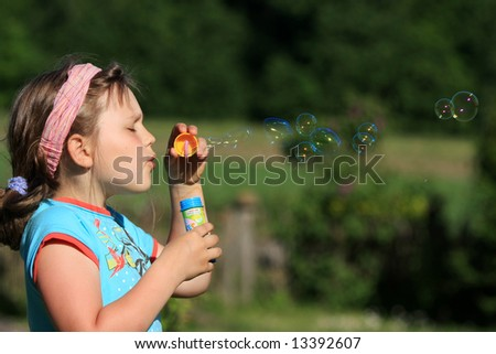 Girl blowing soap bubbles outdoors