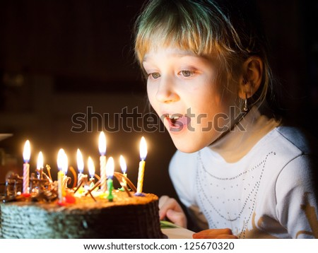 Girl blows out the candles - stock photo