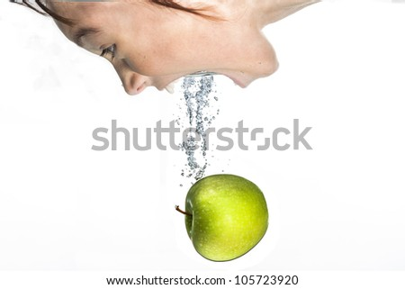 Girl bobs for the apple. - stock photo