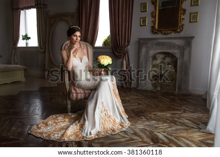 girl bride in a white evening dress in an expensive interior with flowers