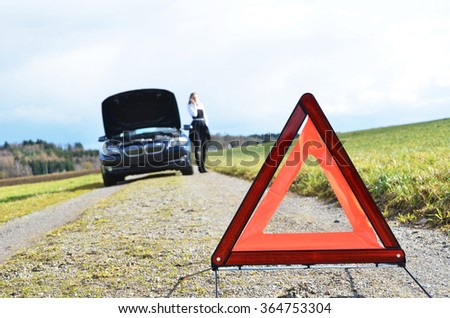 Girl, broken car and triangle - stock photo