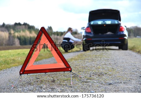 Girl, broken car and warning triangle