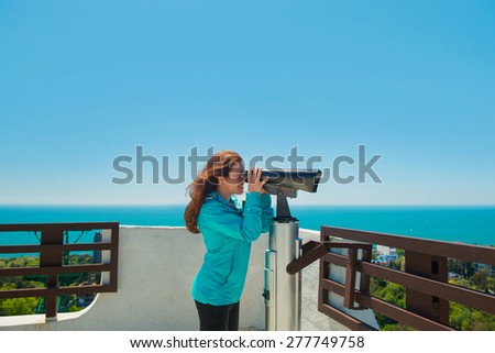 Girl brown-haired woman looks through a telescope on the Observatory and smiles - stock photo