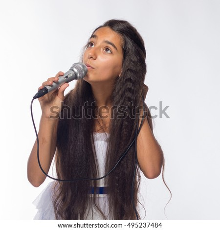 Girl brunette in a white dress with a microphone on a white background