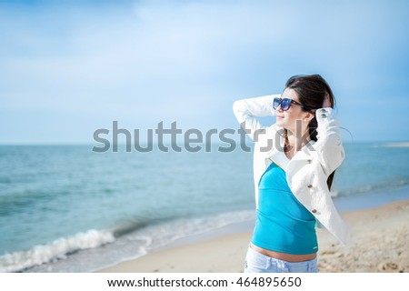 Girl brunette in a white jacket, straightens her hair and stares into the distance on the beach. Travel and Vacation.