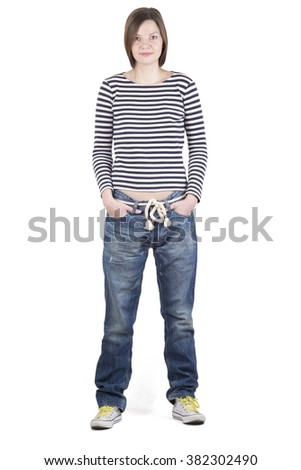 Girl brunette standing in a striped shirt and blue jeans on a white background. White sneakers - stock photo