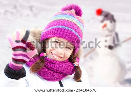 Girl building a snowman - stock photo