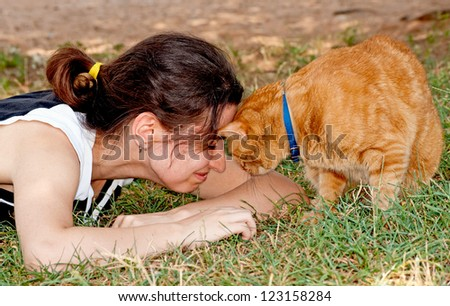 Girl butting heads with her ginger cat - stock photo