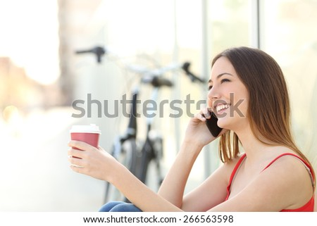 Girl calling on the mobile phone and drinking coffee sitting in a park with a bicycle in the background - stock photo