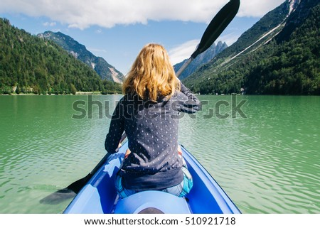 Girl canoeing on a lake in the mountains on a sunny day