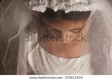 Girl celebrating her First Communion. Her face is covered by her veil, and she is looking down. Sad, serious feeling. Horizontal photo - stock photo