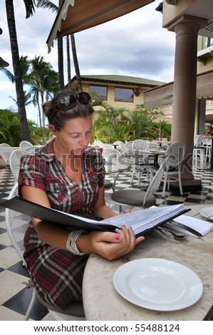 girl checking out menu at the restaurant - stock photo