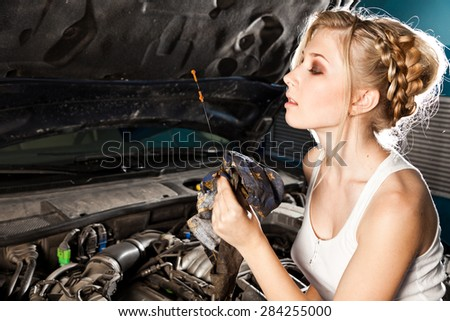Girl checks the oil level with dipstick in their own broken car - stock photo