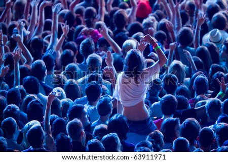 girl cheering with crowd and sitting upon the shoulders of her friend - stock photo