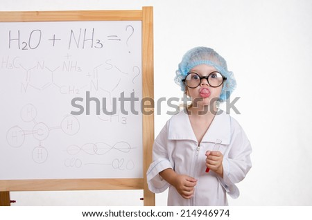 Girl chemist at the blackboard showing tongue - stock photo
