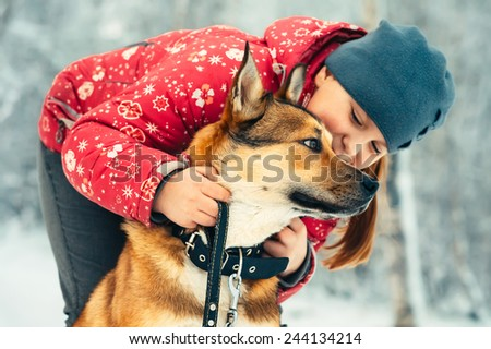 Girl Child and Dog hugging and playing Outdoor Lifestyle Friendship concept Winter nature on background - stock photo