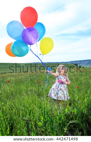 Girl child holding balloons in strong wind, standing in green field on background sky