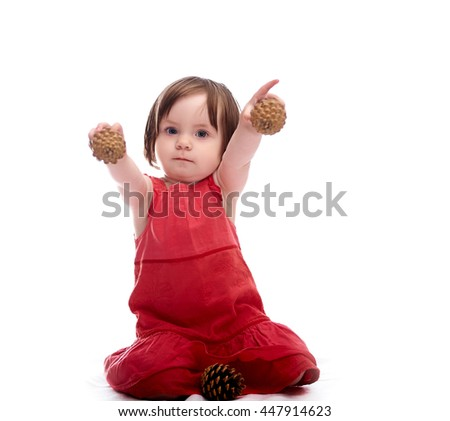 Girl child in red dress isolated on a white background playing with cones