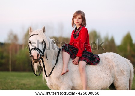 Girl child is sitting on a small white horse looking into the camera Outdoors - stock photo