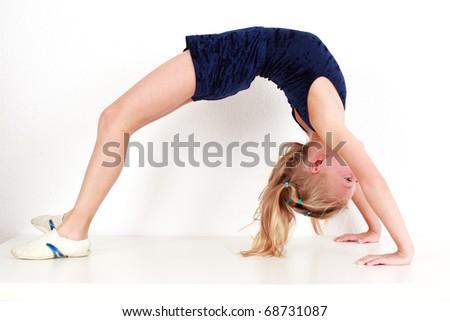 Girl child performing backward bend gymnastics on white background - stock photo