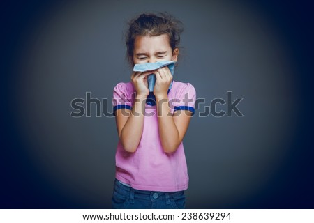 girl child sneezes into a handkerchief on a gray background cross process - stock photo
