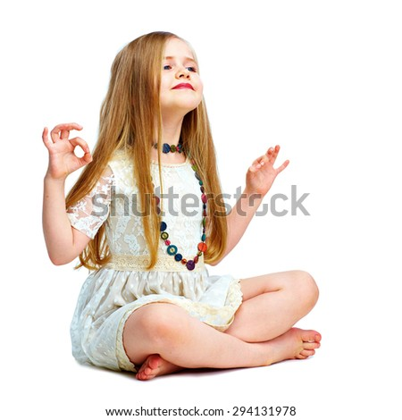girl child with long blond hair siting on a floor in yoga lotus pose. fashion portrait isolated on white background.  - stock photo
