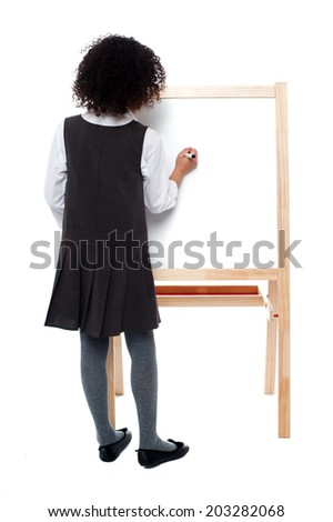 Girl child writing with marker on white board - stock photo