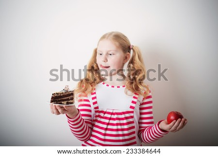 Girl choose from sweet cake and red apple - stock photo