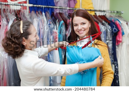Girl chooses evening dress at clothing store. Shop consultant helps her - stock photo