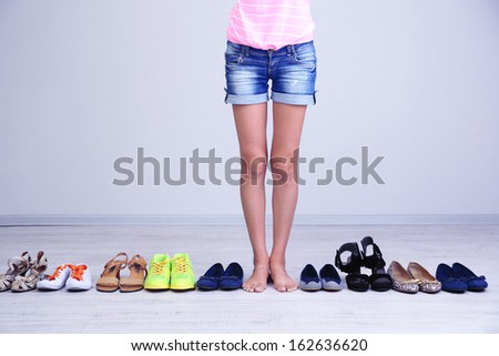 Girl chooses shoes in room on grey background - stock photo