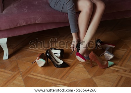 Girl choosing a pair of high heels shoes. Sitting on pink velvet elegant sofa. Hard choice.  Beautiful legs. Shopping at store. Choosing perfect pair