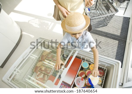 girl choosing ice cream at convenience store - stock photo