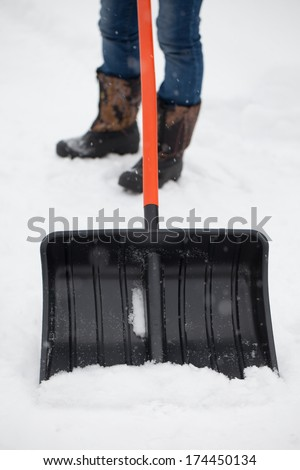 Girl cleaning snow with a shovel  - stock photo