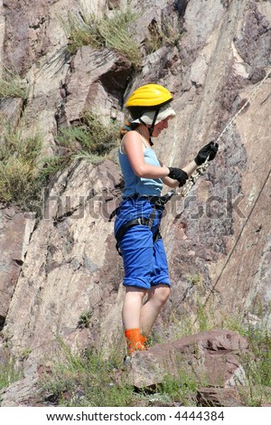 girl climber at a rock in equipment