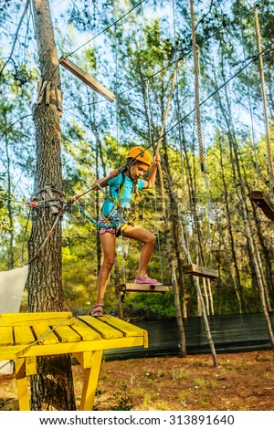 Girl climbing in adventure park is a place which can contain a wide variety of elements, such as rope climbing exercises, obstacle courses and zip-lines. - stock photo