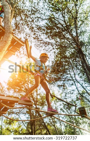 Girl climbing in adventure park is a place which can contain a wide variety of elements, such as rope climbing exercises, obstacle courses and zip-lines.