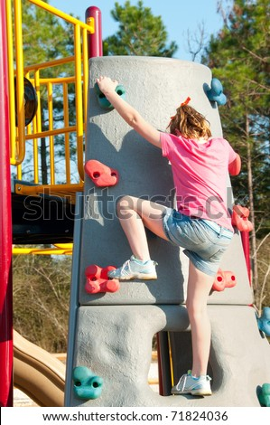 girl climbing up wall in park - stock photo