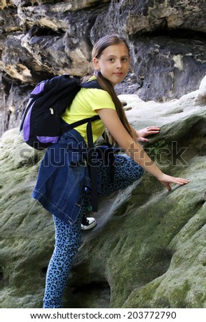 girl climbs on a rock with a backpack - stock photo