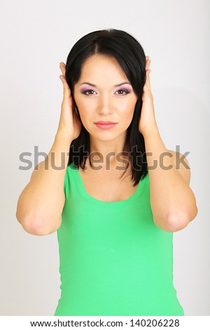 Girl closes ears on grey background - stock photo