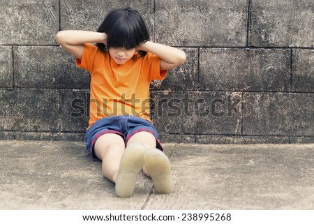 girl closing her ears sitting on grunge room - stock photo