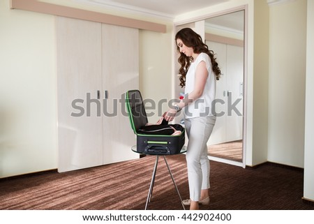 Girl collects a suitcase in a hotel room.