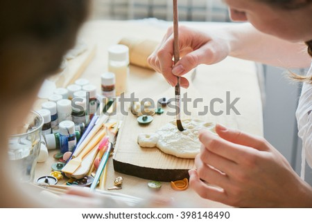 Girl colors the handmade dough - stock photo