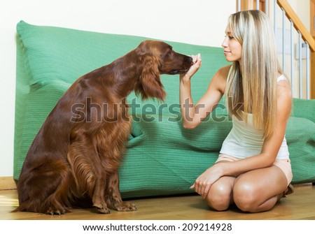 girl communicating with Irish setter at home
