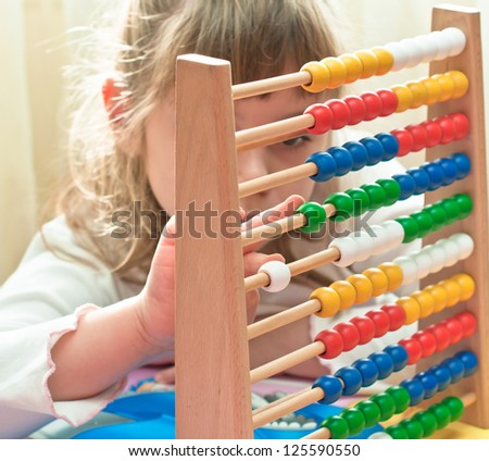 Girl contemplates the basics of arithmetic on his abacus. - stock photo