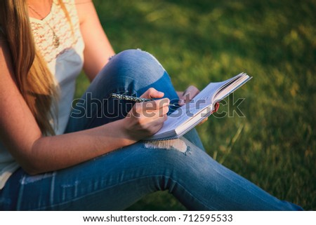 Girl copywriter sitting on the grass with notebook and pen. Woman freelancer writing outdoors.