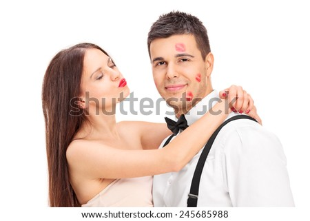 Girl covering a young man in kisses isolated on white background - stock photo